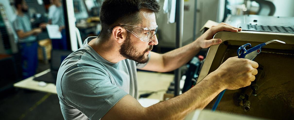Transmetallbau Arbeiter bei Pflege einer CNC Maschine
